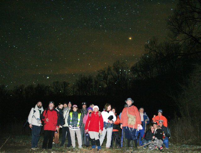 A túra csillagfényes csoportképe, a háttérben a Siriusszal (balra) és a nyugvó Orionnal (jobbra). A jobbra fent látható fényes, narancsos színű csillag a Betelgeuse, az alfa Orionis.