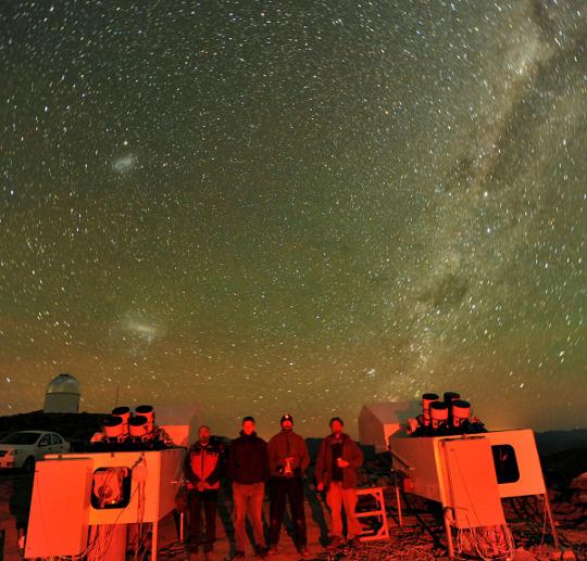A hét csillagászati képe éjszakai csoportkép: a HAT-Net chilei állomásán mutatja a telepítésen résztvevőket. Fantasztikus égbolt látható fölöttük, a Tejút szélesen hömpölygő sávjától balra két galaxisszomszédunk, a Nagy Magellán-felhő és a Kis Magellán-felhő látható.