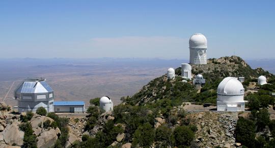 A Kitt Peak National Observatory. A kép bal szélén az előtérben áll a 3,5 méteres WIYN-távcső, hátul, középen a 4 méteres Mayall-távcső. Mindkettőt a bezárás veszélye fenyegeti. Forrás: NOAO/AURA/NSF.