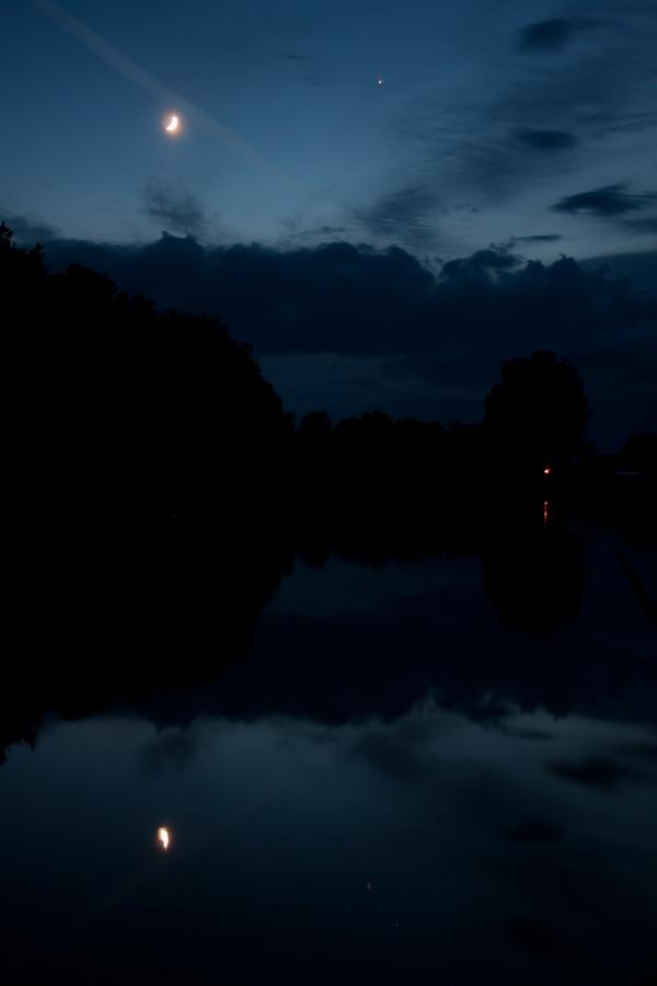 A Hold és a Jupiter fénye csillan meg a Derecskei víztározó víztükrén. Kiss Csongor felvétele 2014. június 2-án készült, az esti szürkületben.