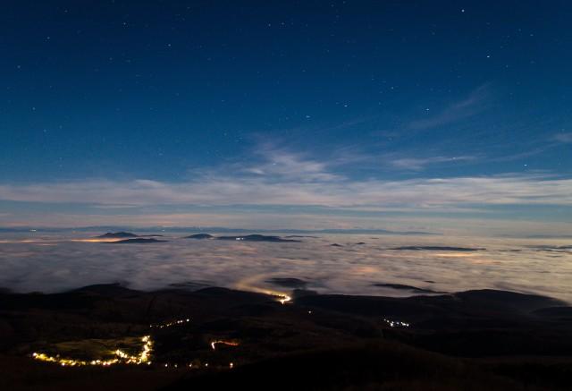 Ilyen volt a látvány a galyatetői kilátóból lepillantva 2015. december 26-án este. A holdfényben úszó felhőtengerből itt is, ott is szigetekként emelkednek ki a hegyek. Bal oldalon jól láthatjuk a Karancs hármas púpját, tőle jobbra a Medvest, a távolban, a horizonton pedig a Magas-Tátra csipkézett ormait is felfedezhetjük. A települések világítása sejtelmesen szüremlik át a ködpaplanon. Minderről tudomást sem vesz a Nagy Göncöl, melynek jellegzetes alakzatát mindenki könnyen felfedezheti. (Nikon D5100, 18-55 mm 20 mm-en, f/3,7, ISO 250, 30 s)